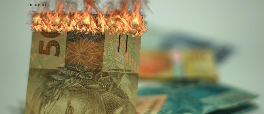 Nota de 50 reais queimando sinalizando a perda inflacionária