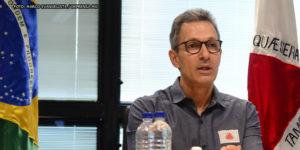Governador de Minas Gerais, Romeu Zema (homem de pele clara, cabelos grisalhos curtos e usando óculos preto e camisa cinza) sentado entre as bandeiras do Brasil e de Minas Gerais.