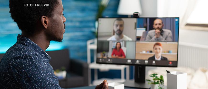 Homem negro com camisa azul de frente para uma tela de computador na qual se vê o rosto desfocado de quatro outras pessoas (dois homens e duas mulheres) que participam de uma reunião por videoconferência.
