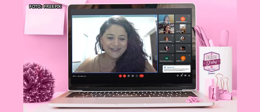 Ambiente de trabalho em tons rosa, com um notebook aberto sobre uma mesa e na tela uma imagem capturada durante a videoconferência na qual o destaque é a consultora de Imagem e Estilo Samara Valamiel (mulher de pele branca com cabelos castanhos e ondulados).