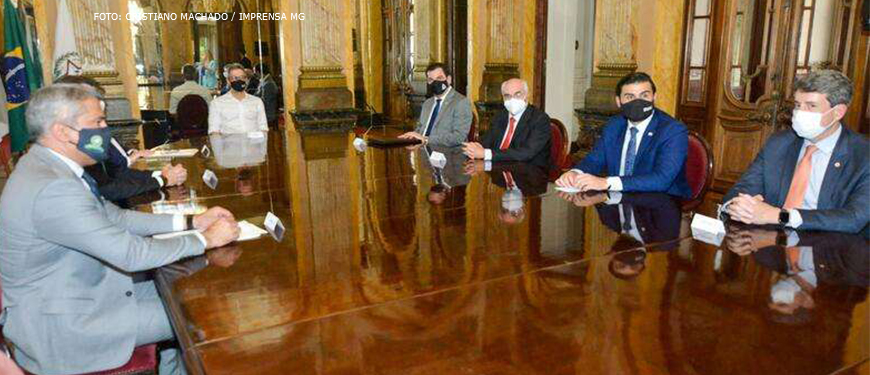 Romeu Zema ao centro da mesa com os demais membros de Poder sentados ao lado em sala do Palácio da Liberdade