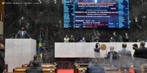 Deputados estaduais conversando na Mesa Diretora e no Plenário da Assembleia Legislativa de Minas Gerais. Ao fundo há uma parede em granito preto e um grande telão que projeta a imagem de um parlamentar que discursa na tribuna.
