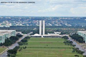 #ImagemAcessível: Imagem aérea de Brasília onde se vê o Congresso Nacional no centro da imagem e os ministérios de cada lado.
